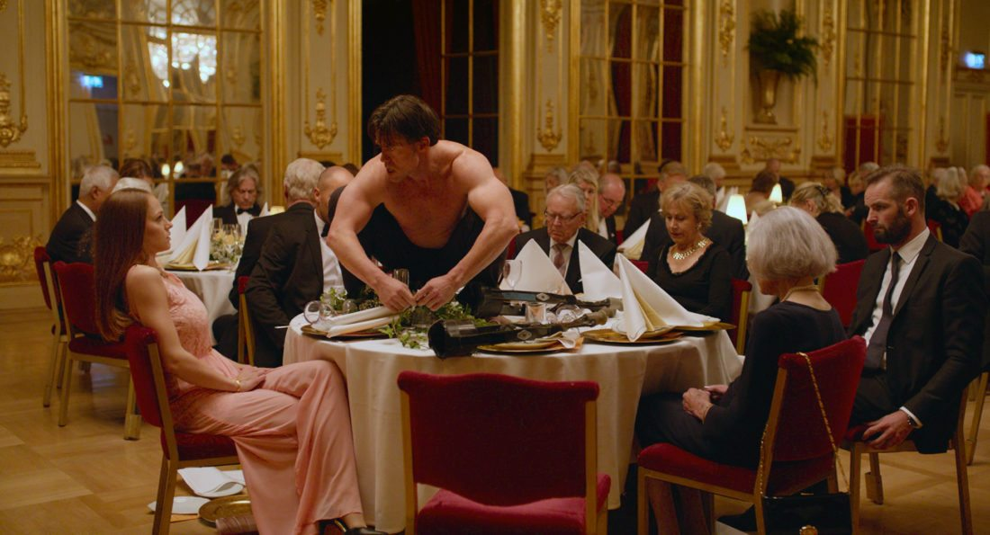 "This image released by Magnolia Pictures shows Terry Notary, center, in a scene from ""The Square."" Notary plays a man who for his performance art, acts like an ape. He's been chosen as the entertainment for a group of well-heeled museum investors, but the interactive bit at a fancy dinner doesn't go as planned as he intimidates and terrorizes the nervous guests. (Magnolia Pictures via AP)"