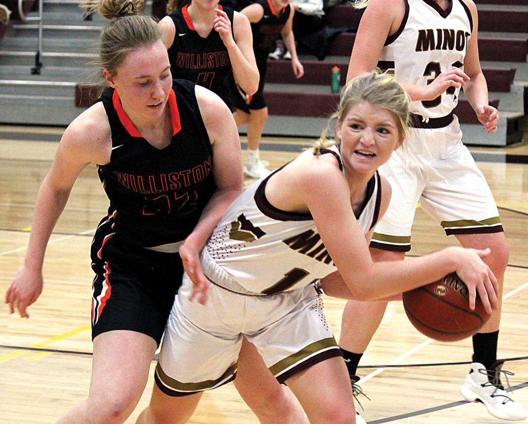 Alex Eisen/MDN Majettes sophomore Becca Tschetter (right) shields the ball away from a Williston defender Friday in a West Region game at Minot High School. The Majettes won 64-51.