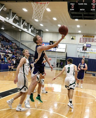 Al Christianson/Photo special to the MDN Bishop Ryan junior Ben Bohl (3) goes up for a reverse layup Saturday evening in a game against Thompson at the Minot Municipal Auditorium.