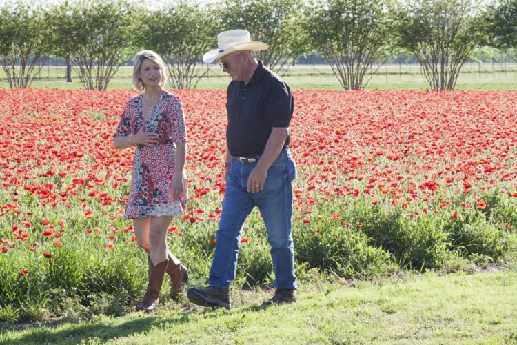 """In this April 4, 2017 photo, TV travel show host Samantha Brown walks through a field of flowers in Fredericksburg, Texas, with John Thomas, the owner of Wildseed Farms. Brown, who's hosted a variety of shows in the past on the Travel Channel, has a new series premiering Jan. 6 on PBS called """"Places to Love."""" (Samantha Brown via AP)"""
