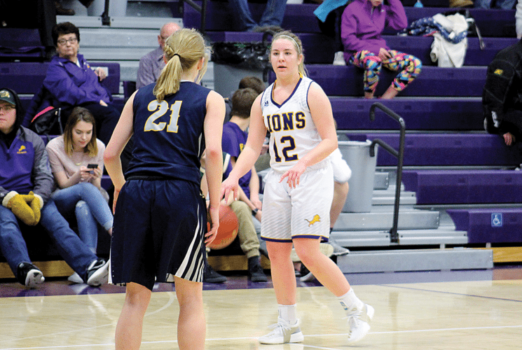 Ashton Gerard/MDN Bishop Ryan's Sealy Rovig (12) looks for the pass around Mohall-Lansford-Sherwood's Leah Feland (21) Friday at Bishop Ryan. The Lions defeated the Mavericks 54-37.