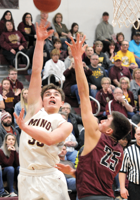 Magi sophomore Jaxon Gunville (left) attempts a layup over Bismarck High defender Tanner Davis (25) Saturday in a WDA basketball game played at Minot High School.   Alex Eisen/MDN