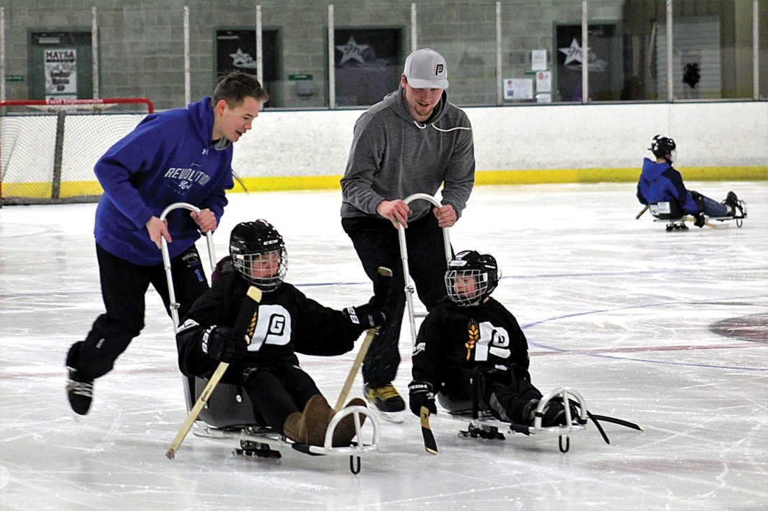 Ashton Gerard/MDN Volunteers push children on sleds Saturday at the Prairie Grit Adaptive Sports sled hockey practice at Maysa Arena.