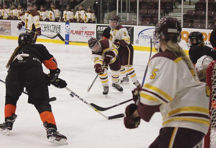 Alex Eisen/MDN Minot High junior forward Parker Larson (18) takes a shot through traffic in a WDA girls hockey game Tuesday evening against Williston at Maysa Arena.