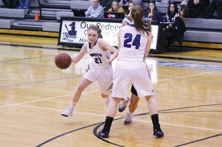 Ashton Gerard/MDN Our Redeemer's Annie Folden (24) sets the pick for Karolynn Winger (21) at home against Mohall-Lansford-Sherwood Tuesday. The Mavericks defeated the Knights 54-49.
