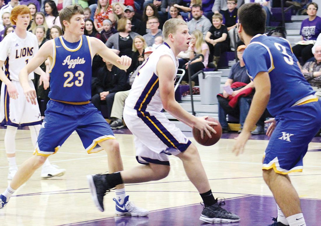 Ashton Gerard/MDN Bishop Ryan's Anthony Vetter (center) dribbles past Velva's Hayden Lee (23) in a game at Bishop Ryan Tuesday. The Lions defeated the Aggies 67-48. Vetter scored 15 points for the Lions, second behind Ben Bohl with 26.