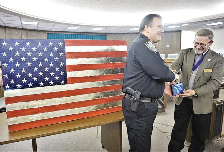 Jill Schramm/MDN A representative of the Minot Moose Lodge presents a plaque and a flag to Minot Police Chief Jason Olson, left, in recognition of the work of the police department during the Minot City Council meeting Monday. A police officer had noticed a similar flag at the Moose Lodge and commented it would look good at headquarters. A member of the Dakota Moose Association responded by purchasing the flag to donate to the department in conjunction with the Moose Heart of the Community program honoring community heroes.