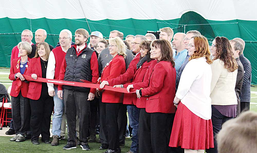 """Ashton Gerard/MDN Members of the Minot State University staff stand with community representatives and donor representatives for a ribbon cutting ceremony Wednesday evening on the field at Herb Parker Stadium under the newly inflated """"bubble"""" at Minot State University."""
