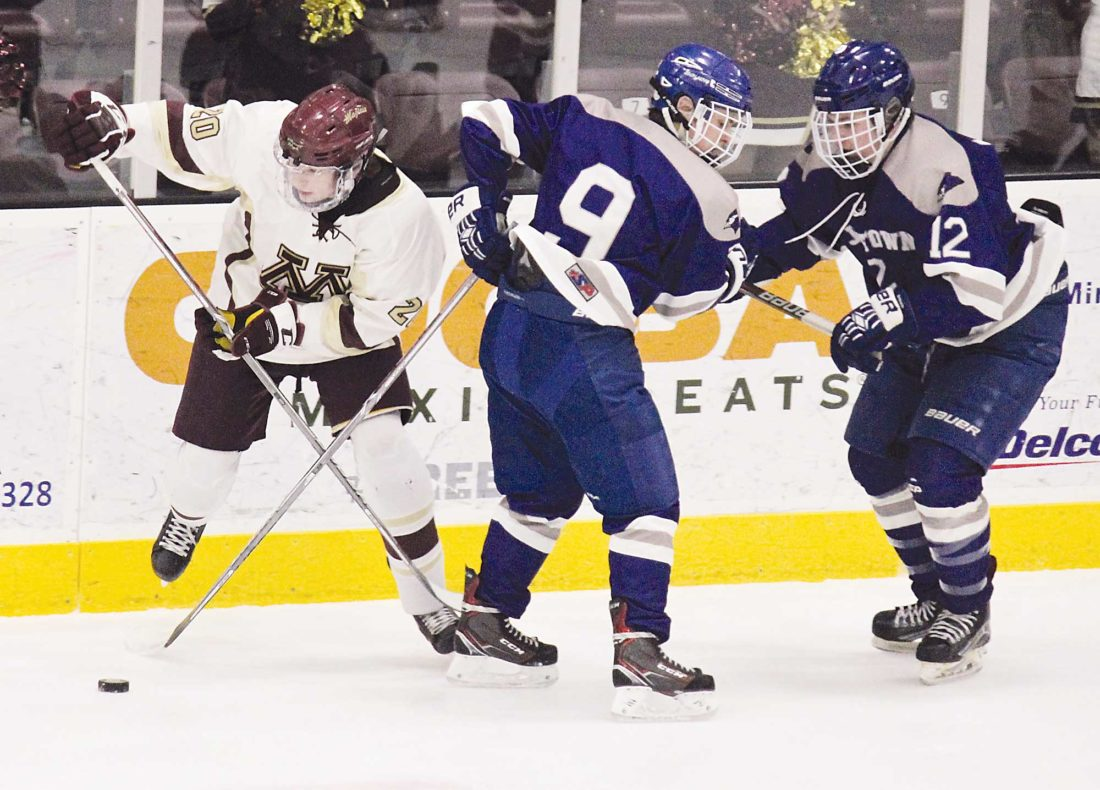 Alex Eisen/MDN Minot High junior Kyler Stenberg (20) gets around Jamestown skaters Bryce Nelson (9) and Jace Thompson (12) in a West Region game played Friday at Maysa Arena.
