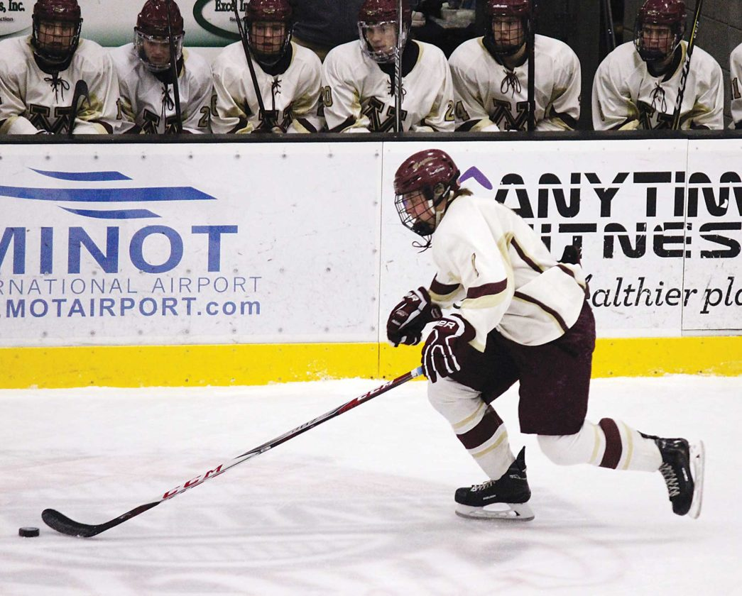 Alex Eisen/MDN Minot High junior Ian Abrahamson skates up the boards in a game against Jamestown on Friday at Maysa Arena in Minot.