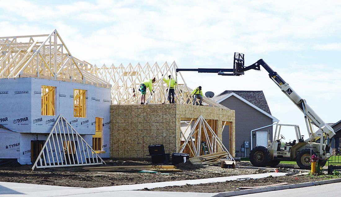 File Photo Workers erect houses in southeast Minot last May.