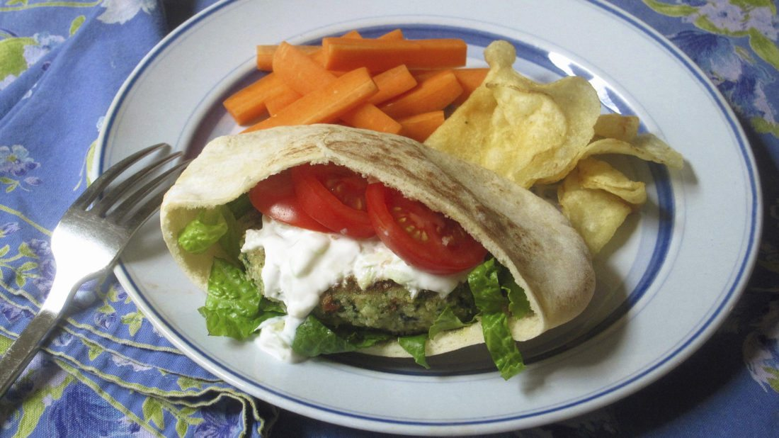 This Dec. 29, 2017 photo shows a spinach and feta burger with a cucumber yogurt sauce in New York. This dish is from a recipe by Sara Moulton. (Sara Moulton via AP)