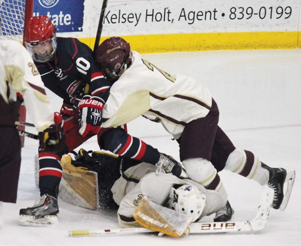 Alex Eisen/MDN Century junior Kirklan Irey (10) and Minot senior Logan Braaten (right) overtop of Magi junior goaltender Odin Nelson in a West Region boys hockey game played Tuesday night at Maysa Arena.