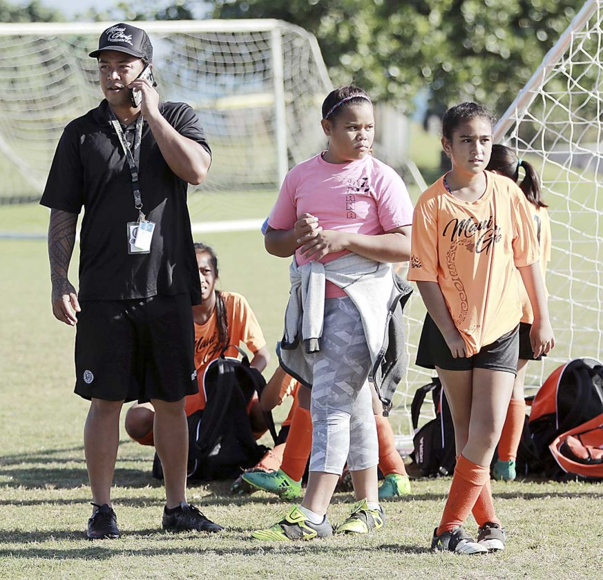 Soccer coach Chazz Kaaihue takes a call on his cellphone next to daughters Leia, left, and Hiilei on Saturday morning at Keopuolani Park in Maui, Hawaii. The false alarm of a missile attack triggered panic for parents and children earlier at a soccer game at the Kahului Community Center. Photo courtesy The Maui News/Chris  Sugidono photo.  Submitted Photo