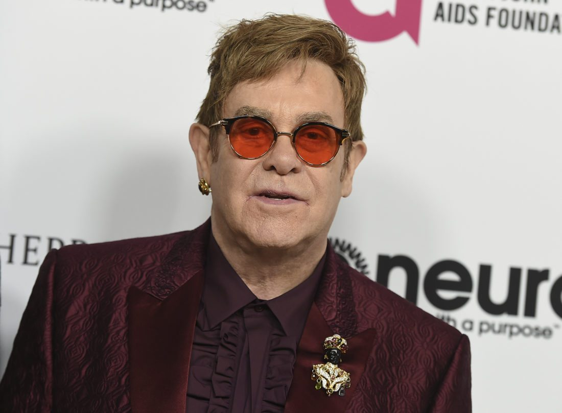 FILE - In this March 25, 2017 file photo, Elton John arrives at Elton John's 70th Birthday and 50-Year Songwriting Partnership with Bernie Taupin celebration in Los Angeles. Elton John is headed to the Grammys to help the organization celebrate its 60th awards show. The Recording Academy announced Wednesday, Jan., 17, 2018 that John and Irish rock band U2 will perform at the Jan. 28 show at Madison Square Garden in New York. (Photo by Jordan Strauss/Invision/AP, File)