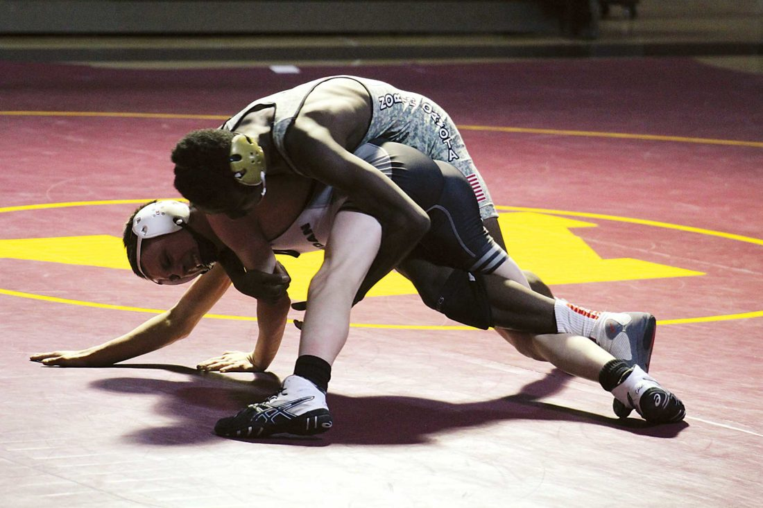 Ashton Gerard/MDN Minot sophomore Corey Hooker II, top, goes for the cradle pin against Mandan's Trevin Yeoman, Thursday in a dual at Minot High.
