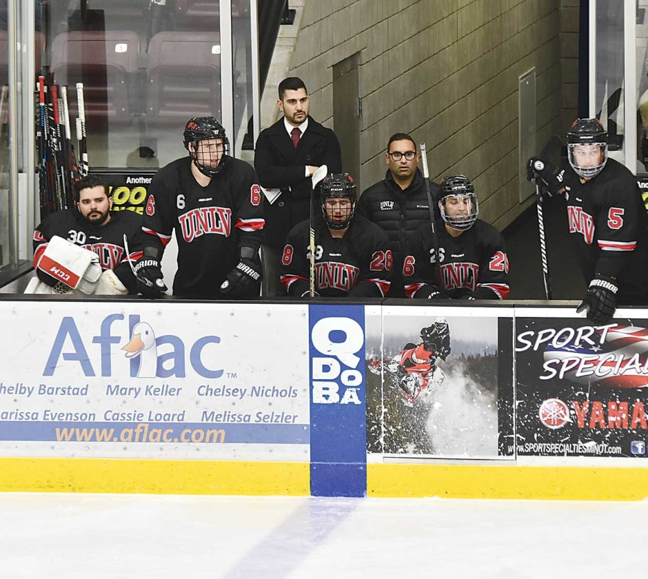 Garrick Hodge/MDN UNLV assistant hockey coach Nick Robone, back center, watches his team during a hockey match against Minot State on Jan. 11 at Maysa Arena.