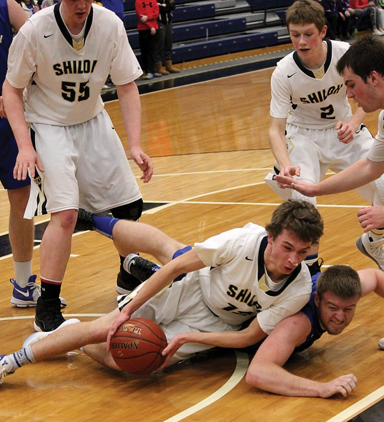 Shiloh Christian's Jonas Mitzel grabs a loose ball while falling on top of Stanley's Kaedyn Hanson in a Class B boys basketball game Saturday evening at the Minot Municipal Auditorium.  Alex Eisen/MDN
