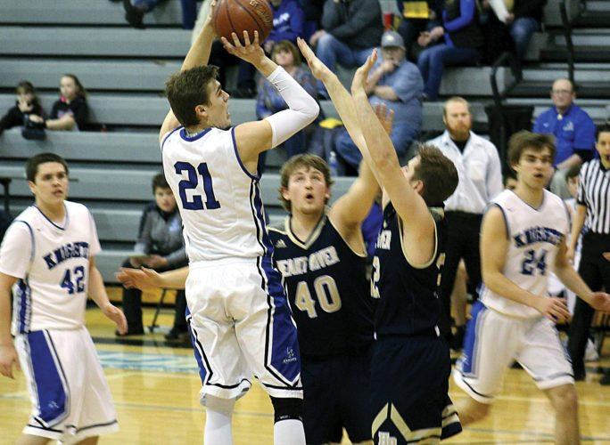 Ashton Gerard/MDN Our Redeemer's senior Jayden Wetzel (21) shoots over two Heart River defenders Saturday at Our Redeemer's.