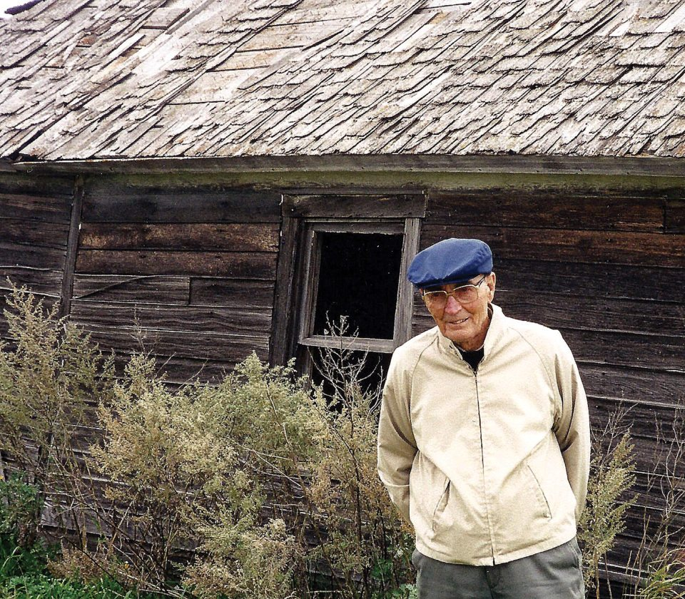 Submitted Photo George Nygaard stands in front of his family's house on their homestead near Maddock when he visited the area with Minot relatives in 1999.