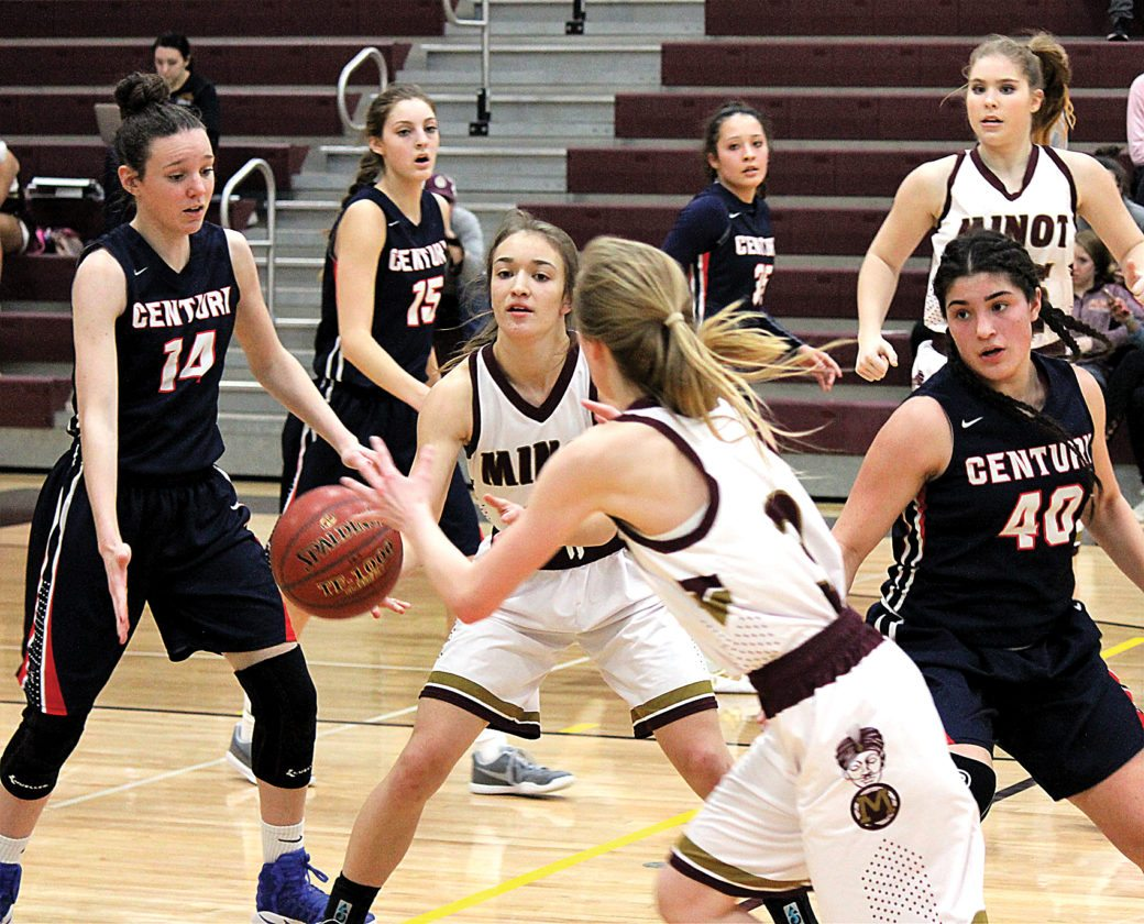 Minot High senior Alli McCoy passes the ball to sophomore teammate Paige Rosencrans in a WDA girls basketball game Monday against Century at Minot High School. Alex Eisen/MDN