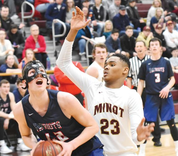Garrick Hodge/MDN Minot High's Devin Mikell (23) guards Bismarck Century's Kade Amundson (42) during a boys high school basketball game Tuesday in Minot.