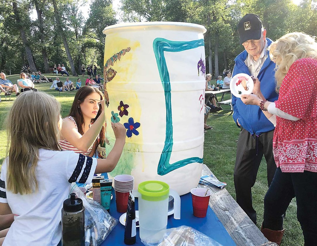 Submitted Photo Rain barrel painting is led by local artist Janie Myers, far right, at the Minot Area Council of the Arts' Arts in the Park event July 6.