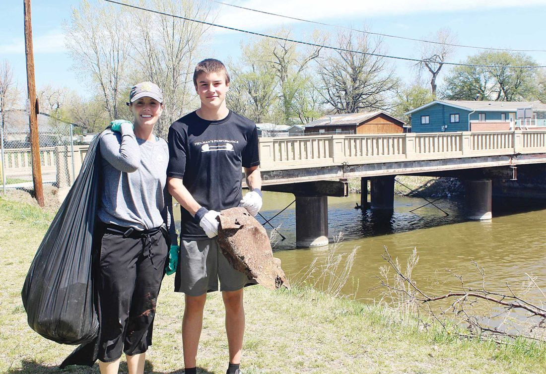Submitted Photo Two of more than 20 volunteers who participated in the May 6 river cleanup in Eastwood Park carry away some of the 1,500 pounds of waste collected.