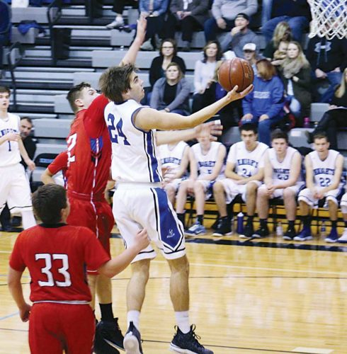 Ashton Gerard/MDN Our Redeemer's Leyton Lang (24) goes up for a layup while guarded by TGU's Shayden Luna (33) and Tanner Schock (32).