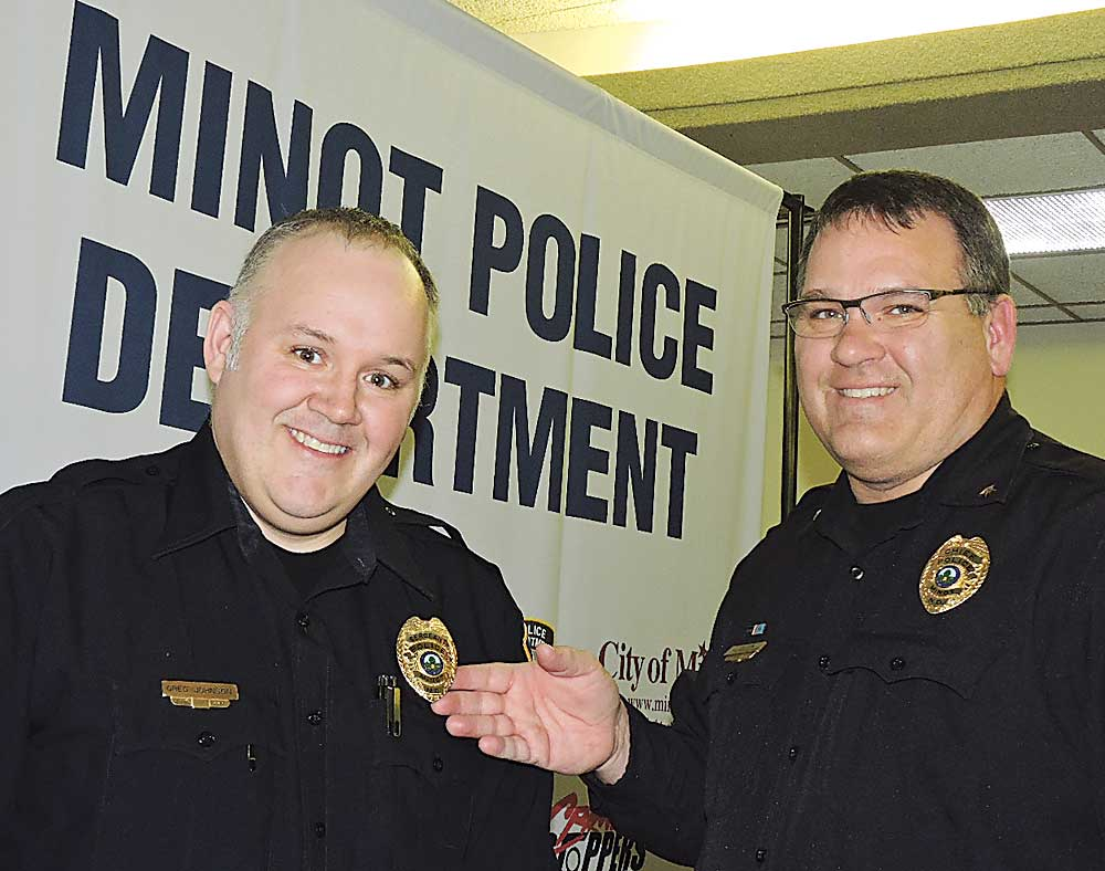 Kim Fundingsland/MDN Senior Officer Greg Johnson, left, receives his promotion to the rank of sergeant from Minot Police Chief Jason Olson during a ceremony at City Hall Wednesday.