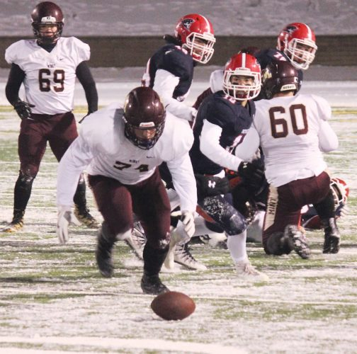 Alex Eisen/MDN Minot High's Logan Krueger (74) recovers a fumble in the Class A state semifinal game against Century this past fall in Bismarck.