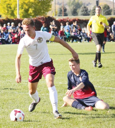 Alex Eisen/MDN Bishop Ryan's JJ Johannsen, playing for Minot High, dribbles the ball around a Century defender in the West Region championship game played earlier this fall in Bismarck. Johannsen signed Wednesday to continue his soccer career at Benedictine College in Kansas.