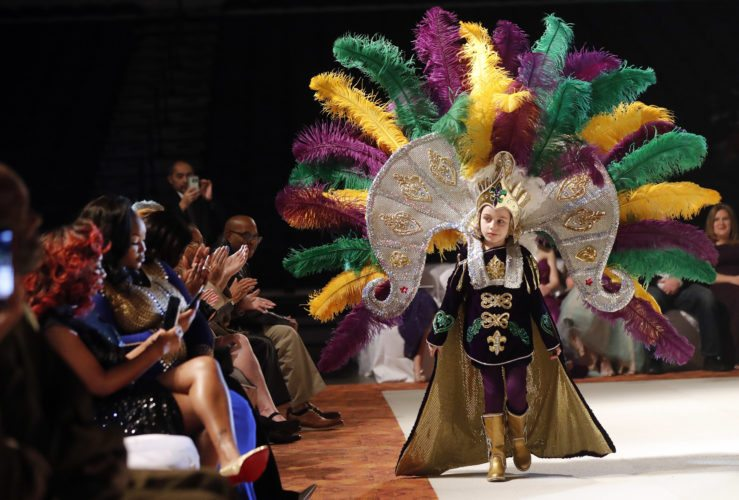 Jack Spittler III, a member of the royal court, walks for the audience at the Little Rascals Mardi Gras Ball in Kenner, La., Thursday, Jan. 25, 2018. (AP Photo/Gerald Herbert)