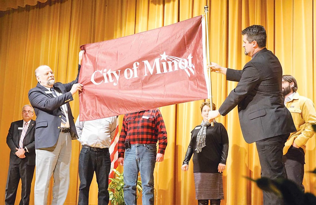 Jill Schramm/MDN Council members Mark Jantzer, left, and Shaun Sipma, right, unfurl Minot's new flag as other city council members and Mayor Chuck Barney, far left, look on during the State of the City event at Magic City Campus Thursday.