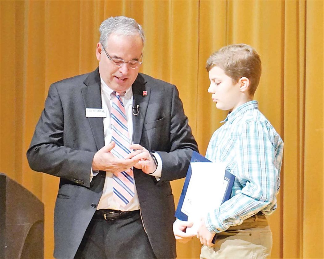 Fifth-grader Grayson Schaeffer reads his essay about his hometown as contest winner  chosen by Mayor Chuck Barney, left.  Jill Schramm/MDN