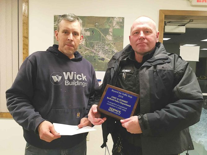 Submitted Photo Berthold's Councilman and Police Commissioner, Travis Sorenson, left, presenting Berthold Police Chief Al Schmidt, right, with the Beyond the Traffic Stop Award in this photo by Marvin Baker of the Kenmare News.
