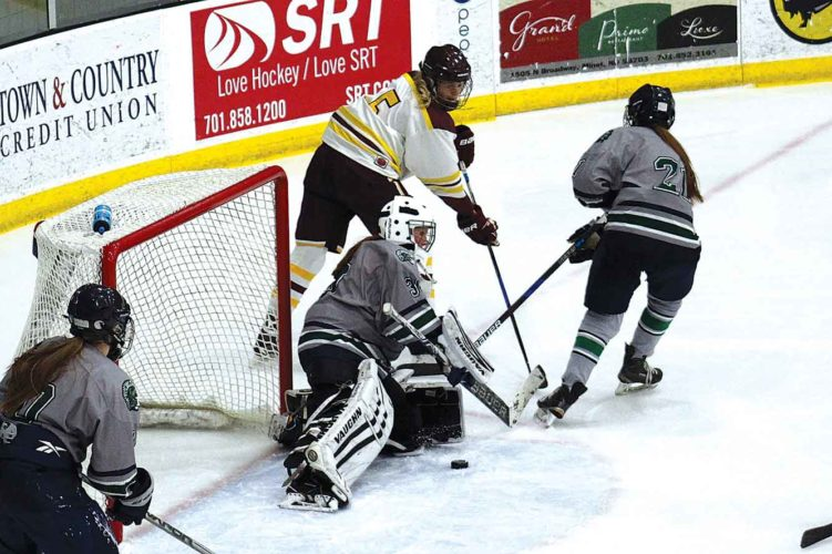Ashton Gerard/MDN Minot High senior Lindsey Larson (5) tries to sneak the puck into the net past Fargo North/South goaltender Lauren Harr, Friday at Maysa Arena. The Majettes fell to FNS 4-1.