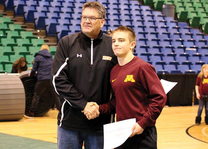 Ashton Gerard/MDN Minot High senior wrestler Brody Armstrong, right, receives a certificate for the Western Dakota Association senior athlete of the year.