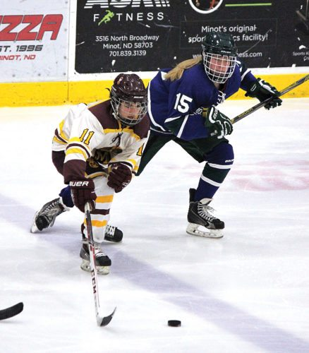 Alex Eisen/MDN Minot High sophomore forward O'Malley Eslinger (11) reaches for a loose puck in a girls hockey game played Saturday afternoon against West Fargo United at Maysa Arena.