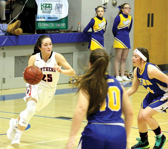 Alex Eisen/MDN Rugby junior guard Anni Stier (25) dribbles the basketball up the floor against Velva's full-court press Saturday evening in the District 11 girls basketball championship game at Velva High School.