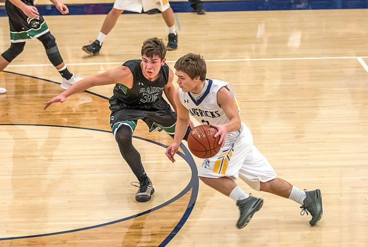 Submitted Photo Kyler McGillis, 34, of St. John, guards Mohall-Lansford-Sherwood's Cole Southam in a high school boys basketball game on Jan. 8. McGillis hit his 1,500th career point during this game. Photo courtesy of Al Christianson.