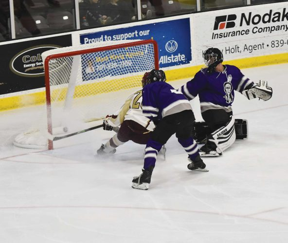 Minot High's Kyler Stenberg (20) scores the opening goal between Minot High and Bottineau/Rugby during a boys high school hockey game Thursday in Minot.  Garrick Hodge/MDN