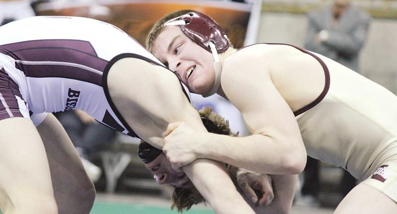 Alex Eisen/MDN Minot High senior Brody Armstrong (right) grabs onto Bismarck High's Adam DeBoer (left) in the 132-pound championship match Saturday at the Fargodome. Armstrong won with a 5-0 decision.