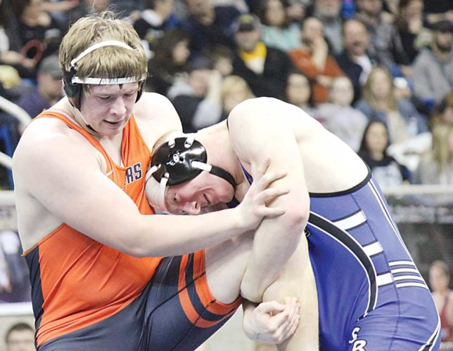 Alex Eisen/MDN Rugby junior DJ Schneibel (left) holds off South Border's Riley Molter (right) in the 285-pound championship match Saturday at the Fargodome. Schneibel won with a 5-0 decision.