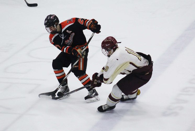 Ashton Gerard/MDN Minot junior Hunter Cope (19) tries to take control of the puck from Dickinson's Peter Pavek (27) Saturday in a boys WDA state qualifying hockey game at Maysa Arena. Pavek scored the third goal of the game for the Midgets.