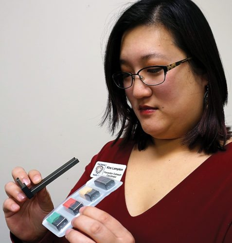 Jill Schramm/MDN Kira Lampton, prevention outreach coordinator with First District Health Unit, holds a Juul e-cigarette, which has a USB plug-in for charging, and a package of flavored nicotine cartridges that snap onto the Juul.