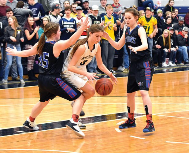 Garrick Hodge/MDN  Mohall-Lansford-Sherwood's Kylie Abernathey (3) tries to dribble out of a double team during a Region 6 girls basketball game Monday at the Minot Auditorium.