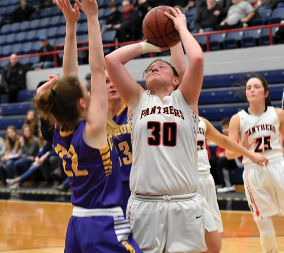 Garrick Hodge/MDN  Rugby's Whitney Gronvold (30) puts up a shot while Berthold's Sara Birdsall (22) defends during a Region 6 girls basketball game Monday at the Minot Auditorium.