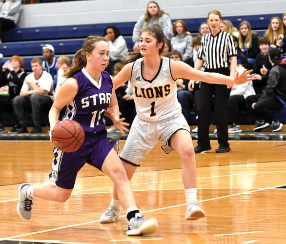 Garrick Hodge/MDN Bottineau guard Sydnie Nelson (10) drives to the basket as Bishop Ryan's Eden Kramer (1) defends her during a Region 6 girls basketball game Monday at the Minot Auditorium.