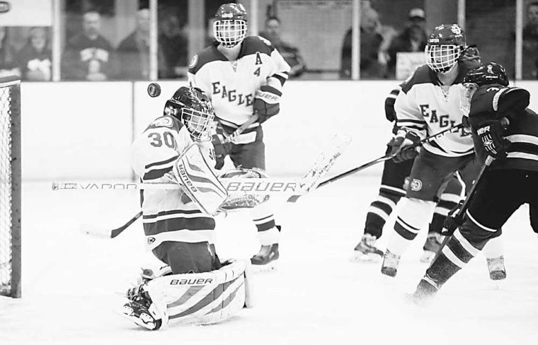 Forum News Service Sydney Peterson of Fargo Davies deflects a shot by Minot during their quarterfinal game of the North Dakota Hockey Tournament on Thursday in Grand Forks.